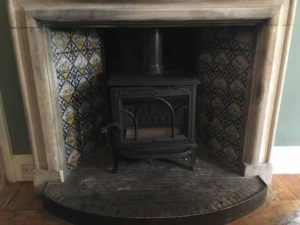 Stove in fireplace with tiled back
