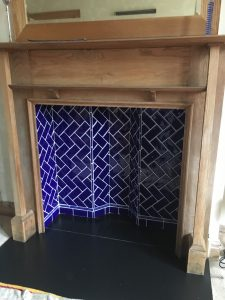 Wood mantlepiece with blue tiles