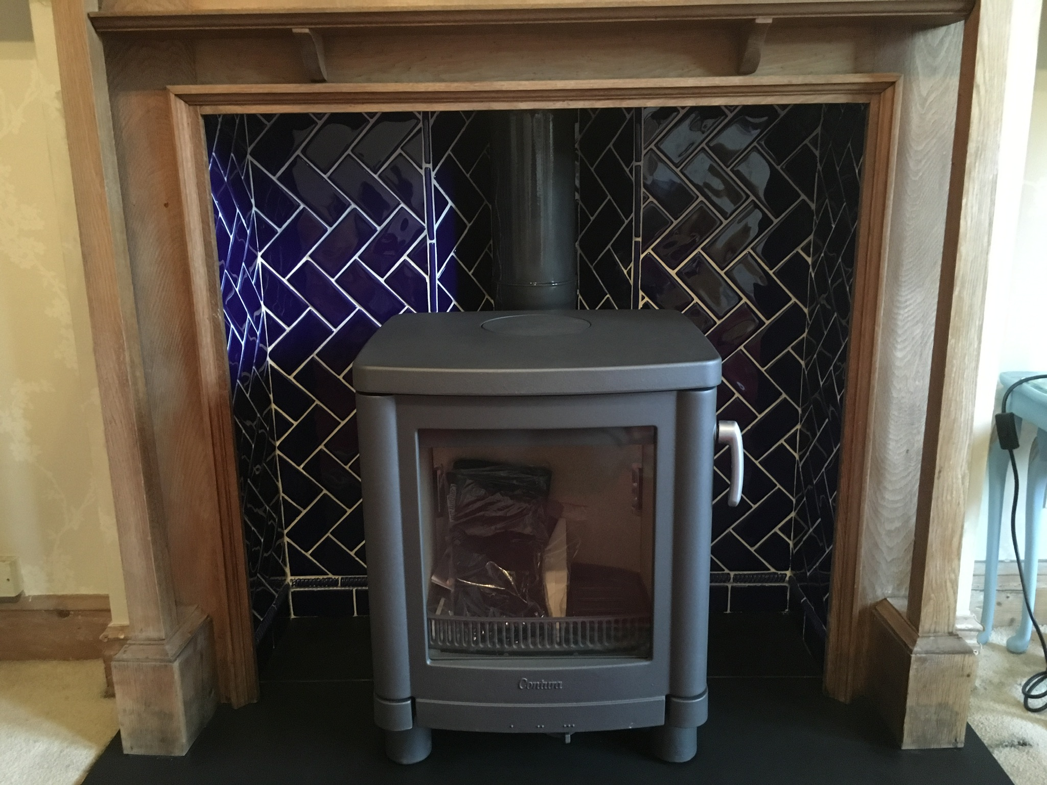 Stove in fireplace with blue tiled back and wood mantlepiece