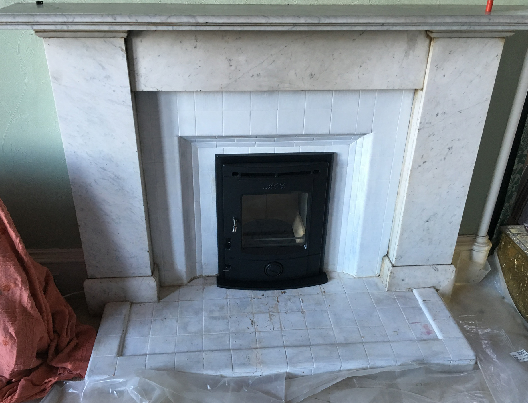 Inset stove with tiles and marble surround