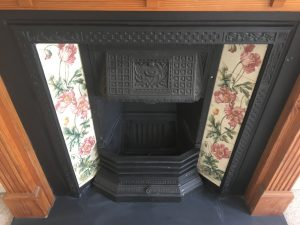 Fireplace close-up showing floral tiles